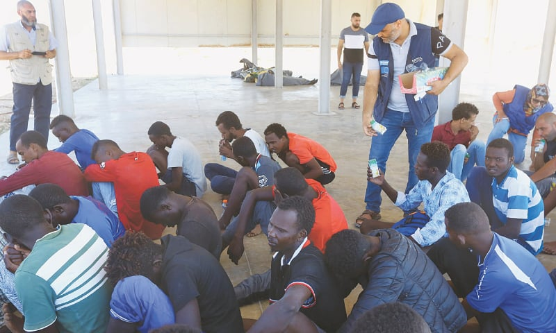 KHOMS (Libya): Rescued migrants receive food at a coast guard point on Tuesday.—AFP