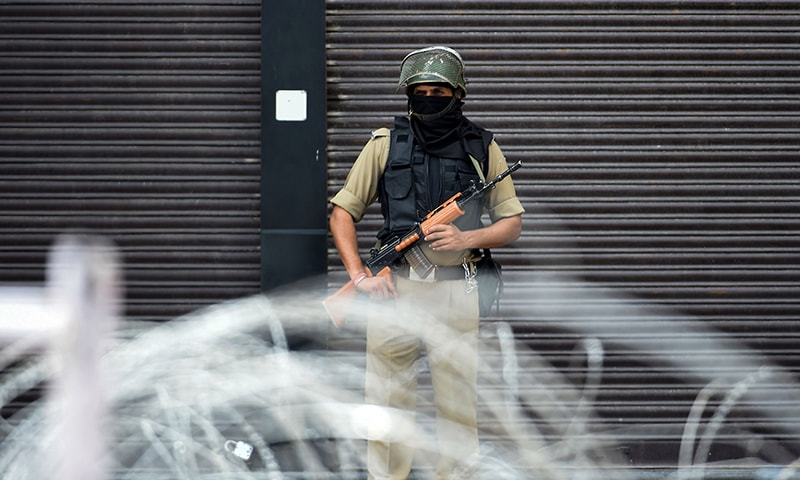 A security personnel stands guard on a street in Srinagar on Wednesday, August 28. — AFP