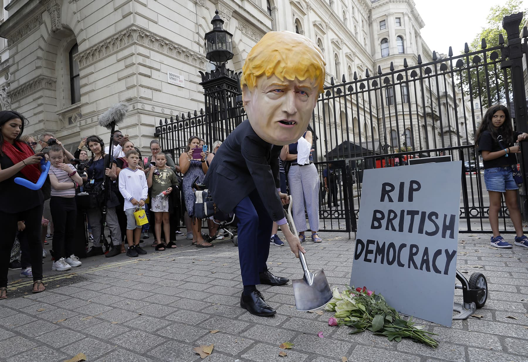 A man in a giant Boris Johnson 'head' digs a grave at the foot of a pretend tombstone outside Downing Street in London on Wednesday. — AP