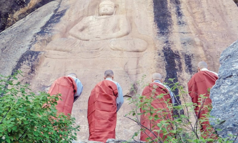 South Korean monks pay respects to a Buddha rock carving in Jahanabad during their visit to Swat on Wednesday. — Dawn