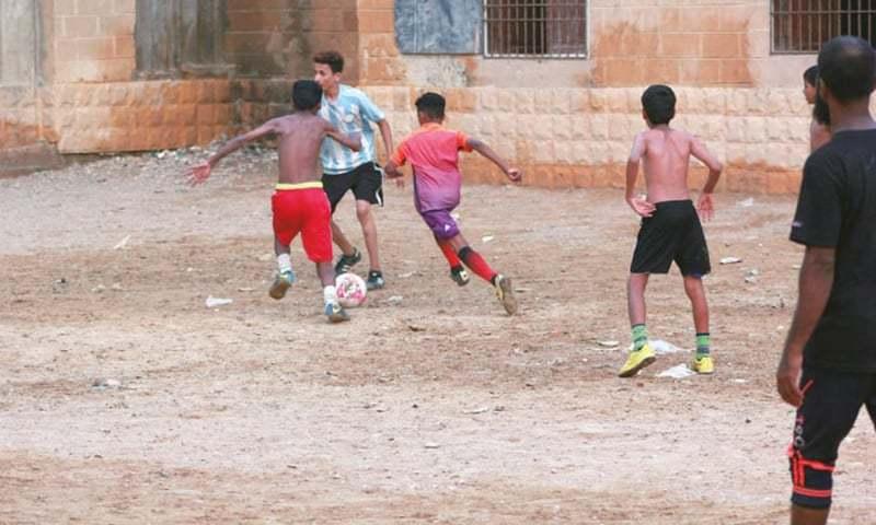 ناہموار چٹانی زمین پر کھیلتے بچے۔