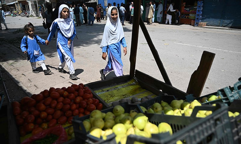 Girls make their way back home from school near the LoC in Chakothi sector, in AJK on Thursday. — AFP