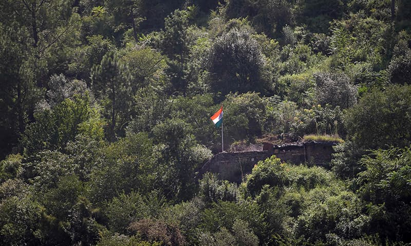 This picture taken from a Pakistani security post shows an Indian flag flying over a military post near the LoC in Chakothi sector, in AJK. — AFP