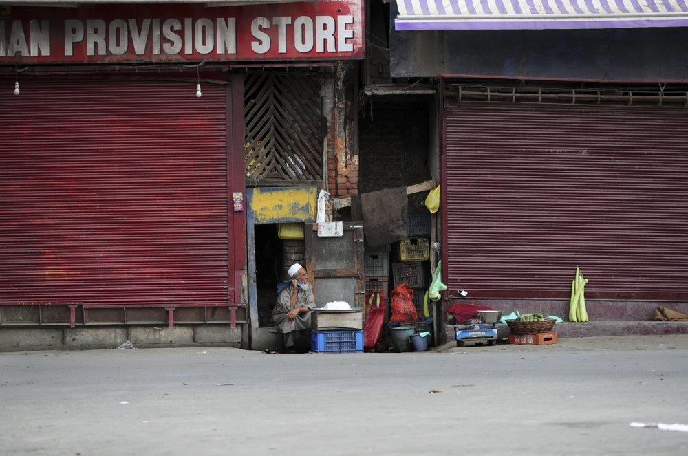 An elderly Kashmiri man sells cheese at a closed market in Srinagar on August 28. ─ AP