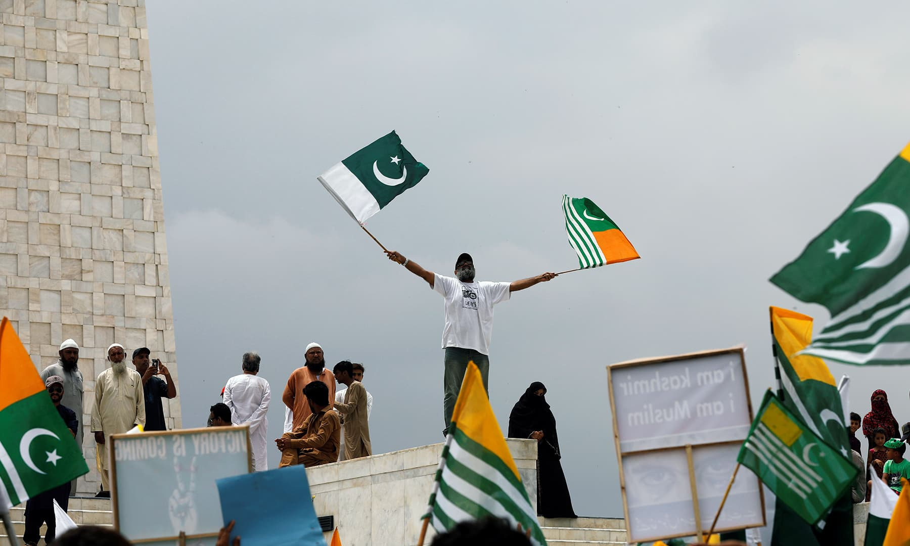 A man waves Pakistan's and Azad Kashmir's flags during a countrywide 'Kashmir Hour' to express solidarity with the people of occupied Kashmir at the Quaid's mausoleum in Karachi. — Reuters