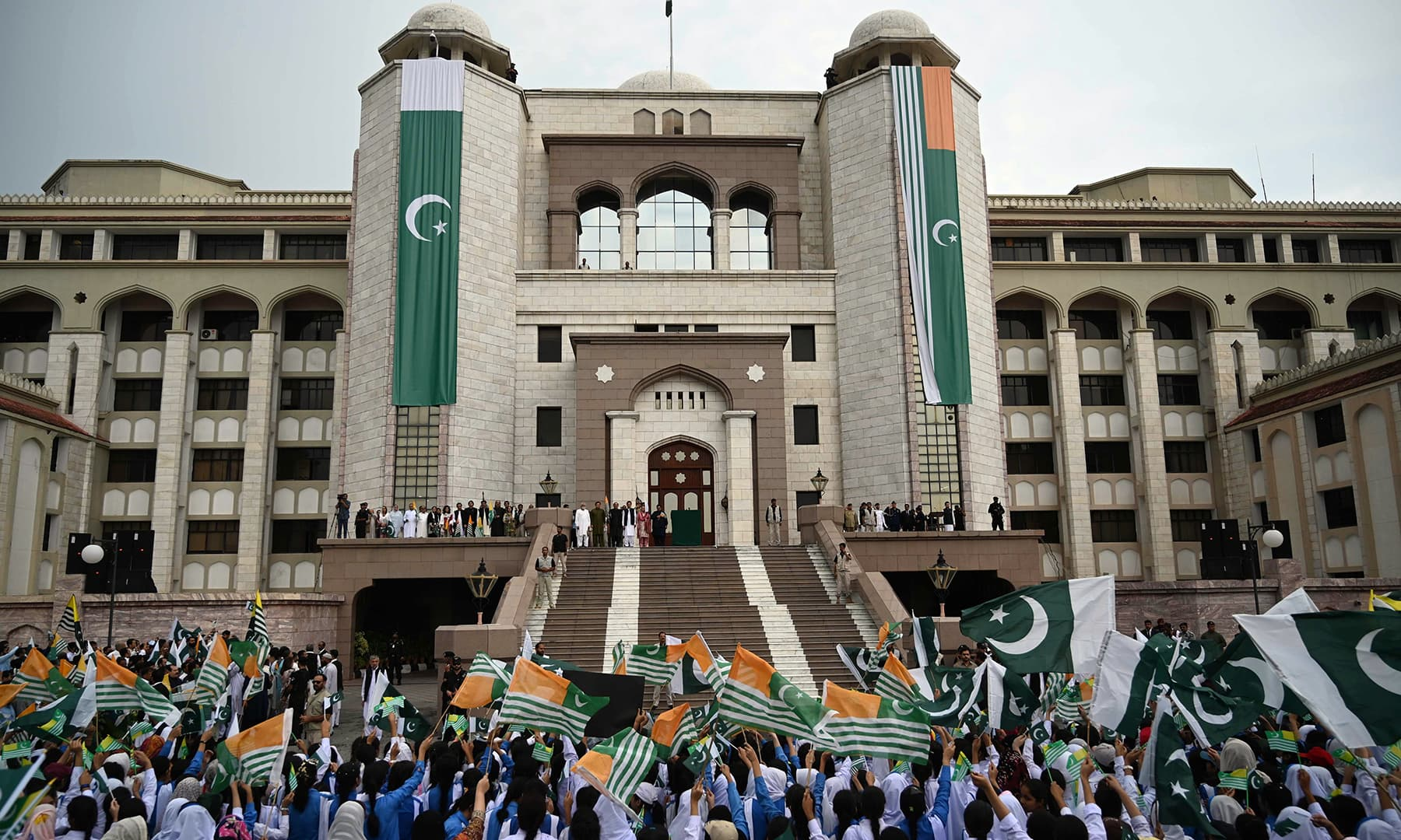 People wave national Pakistan flags and the flags of AJK on the arrival of Prime Minister Imran Khan before his address to the nation outside the Prime Minister Secretariat building in Islamabad. — AFP