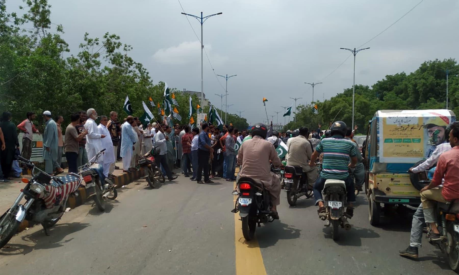 Citizens hold the Pakistani and Kashmiri flags in a demonstration on Karachi's Sharea Faisal. — Photo: Dawn.com