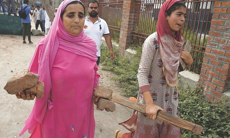 SRINAGAR: Kashmiri women carry stones and pieces of wood during clashes with Indian soldiers in the Anchar area here on Friday.—AFP