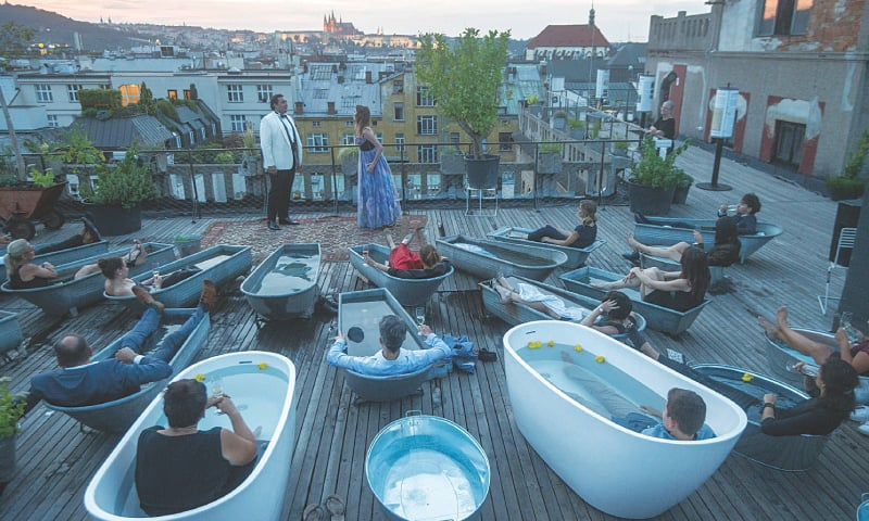 Spectators in bathtubs listen to Czech opera singers Adam Plachetka (left) and  Eva Kyvalova performing parts of Mozart's Don Giovanni on the rooftop of Prague's Lucerna  Palace building.—AFP