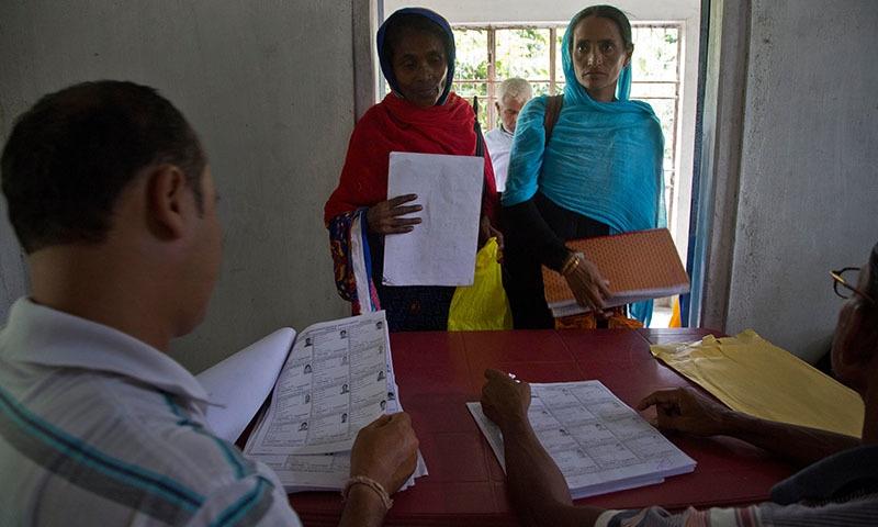 گاؤں کے رہائشی حتمی فہرست جاری ہونے کے بعد اپنا نام تلاش کرنے کے لیے قریبی مراکز پر پہنچے—تصویر: اے پی