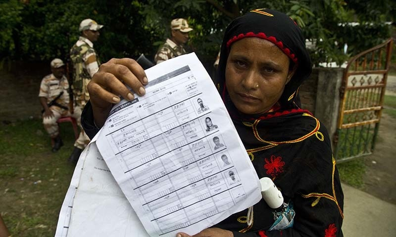 A woman displays a document that shows inclusion of her name in the final list of the National Register of Citizens (NRC) in Pabhokati village in Morigaon district, in the northeastern Indian state of Assam, on Saturday. — AP