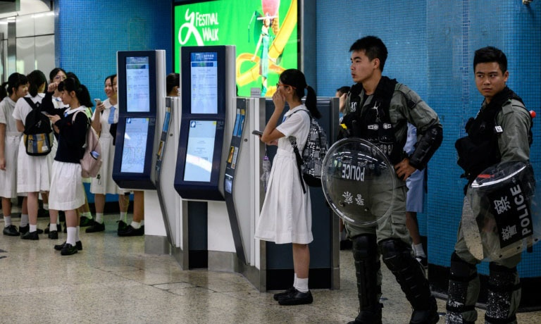 Policemen in riot gear guard MTR stations in Hong Kong. — AFP