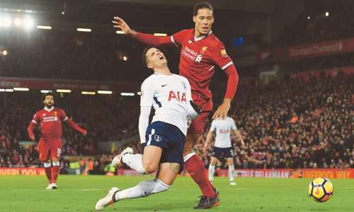 Tottenham Hotspur's Erik Lamela goes down from a tackle by Liverpool's Virgil van Dijk during their Premier League match at Anfield. — AFP
