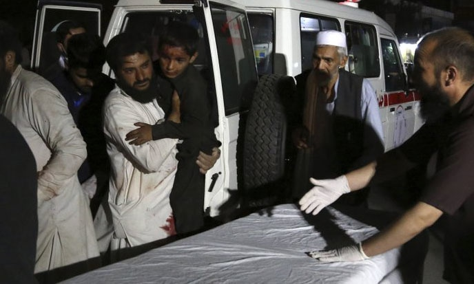 Afghan men carry an injured young boy into a hospital after a large explosion in Kabul, Afghanistan, on Monday night. — AP
