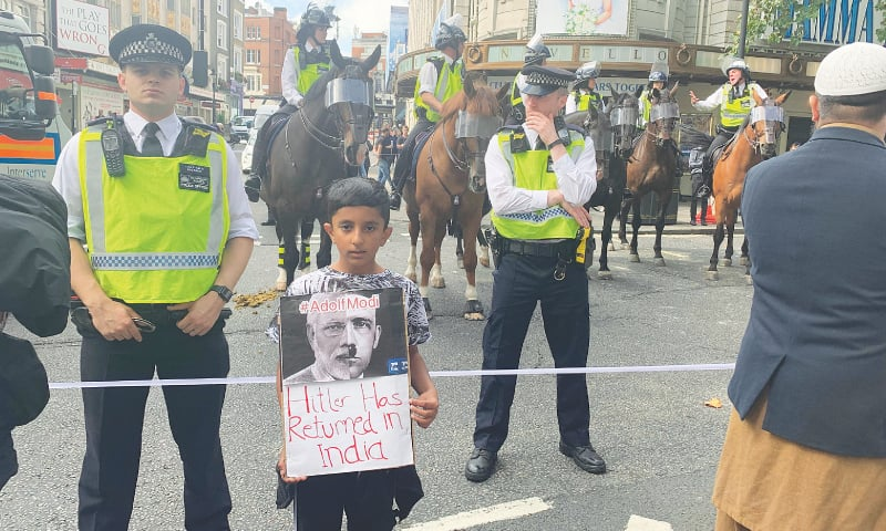 A boy attending the protest holds a placard that describes Narendra Modi as another Hitler. — Dawn