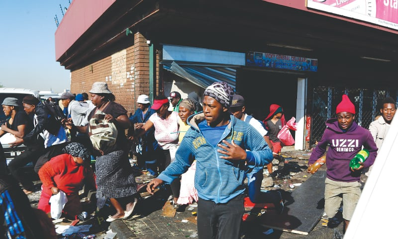 Looters make off with goods from a store in Germiston, east of Johannesburg, on Tuesday. — AP