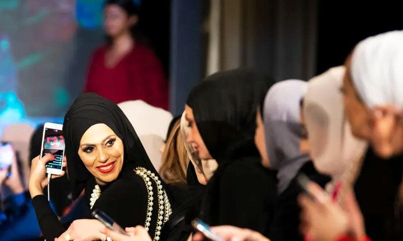 فیشن شو دیکھنے آنے والی خواتین بھی مکمل لباس میں دکھائی دیں —فوٹو: دی گارجین
