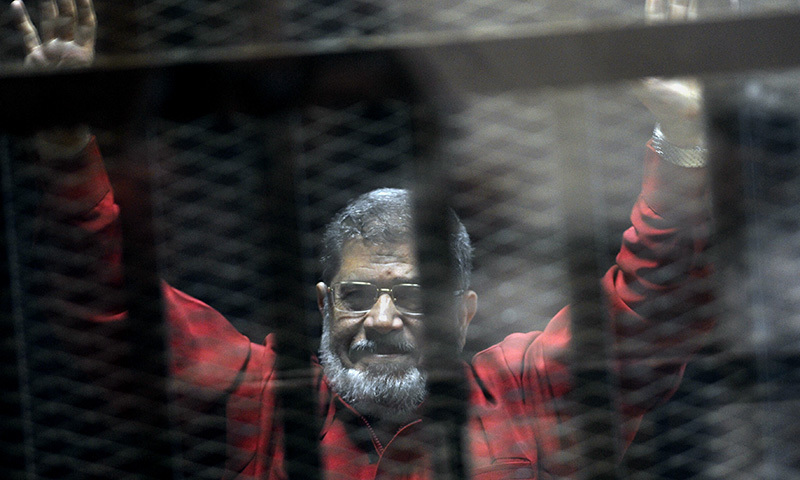 In this June 21, 2015 file photo, former Egyptian president Mohammed Morsi, wearing a red jumpsuit that designates he has been sentenced to death, raises his hands inside a defendants cage in a makeshift courtroom in Cairo. ─ AP/File
