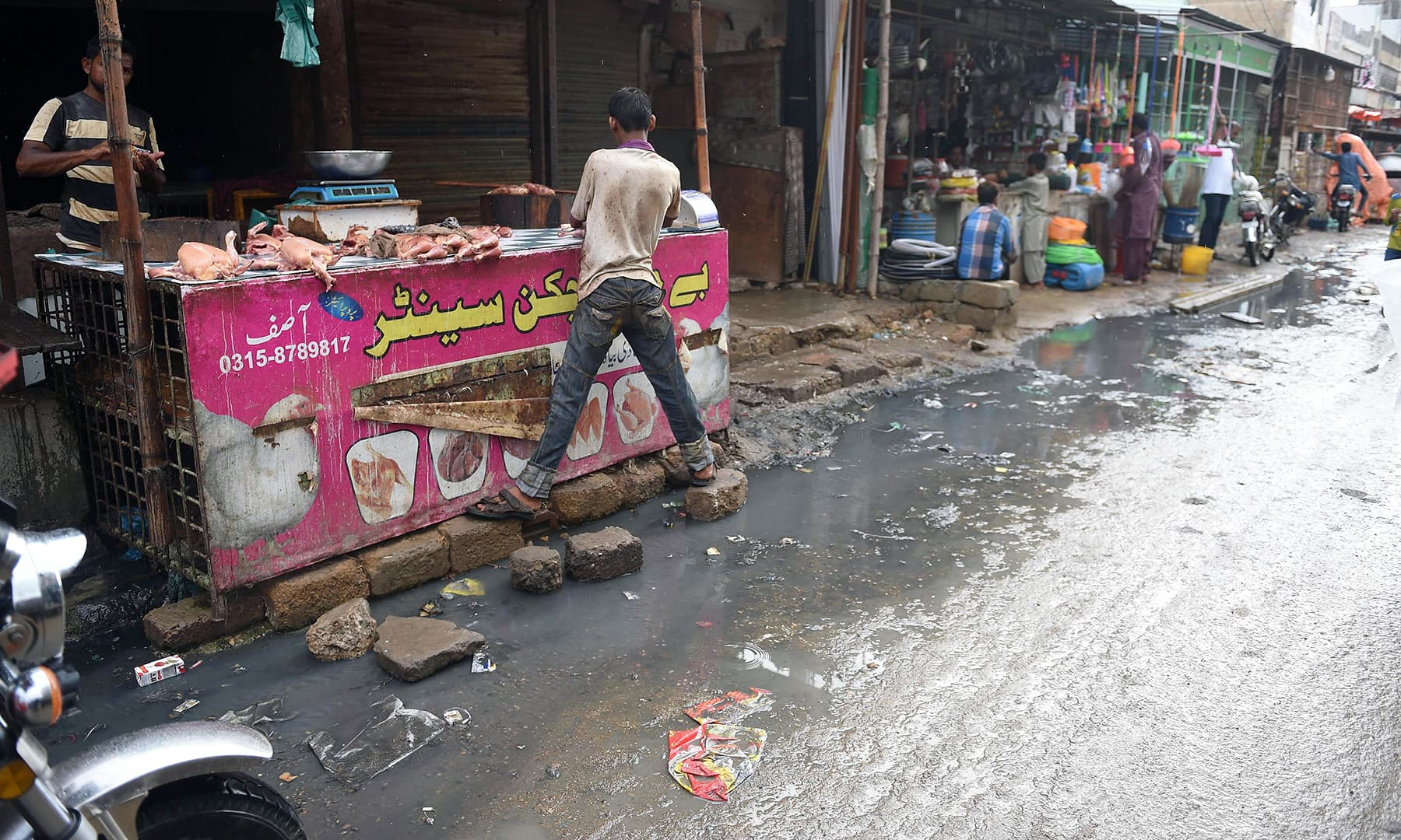 In this picture taken on August 31, a butcher's stall is pictured next to a street flooded with rainwater in a market in Karachi. — AFP