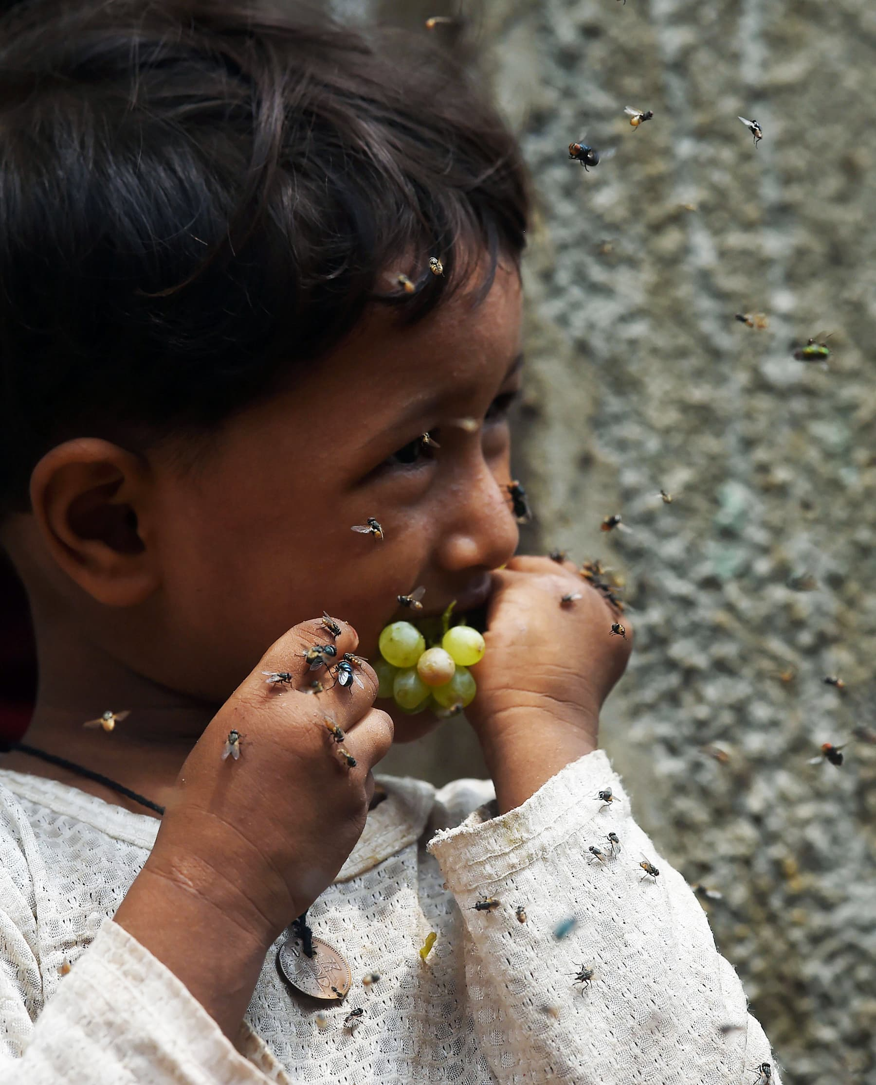 In this picture taken on September 2, a child eats grapes as flies swarm around her in a slum area in Karachi. — AFP