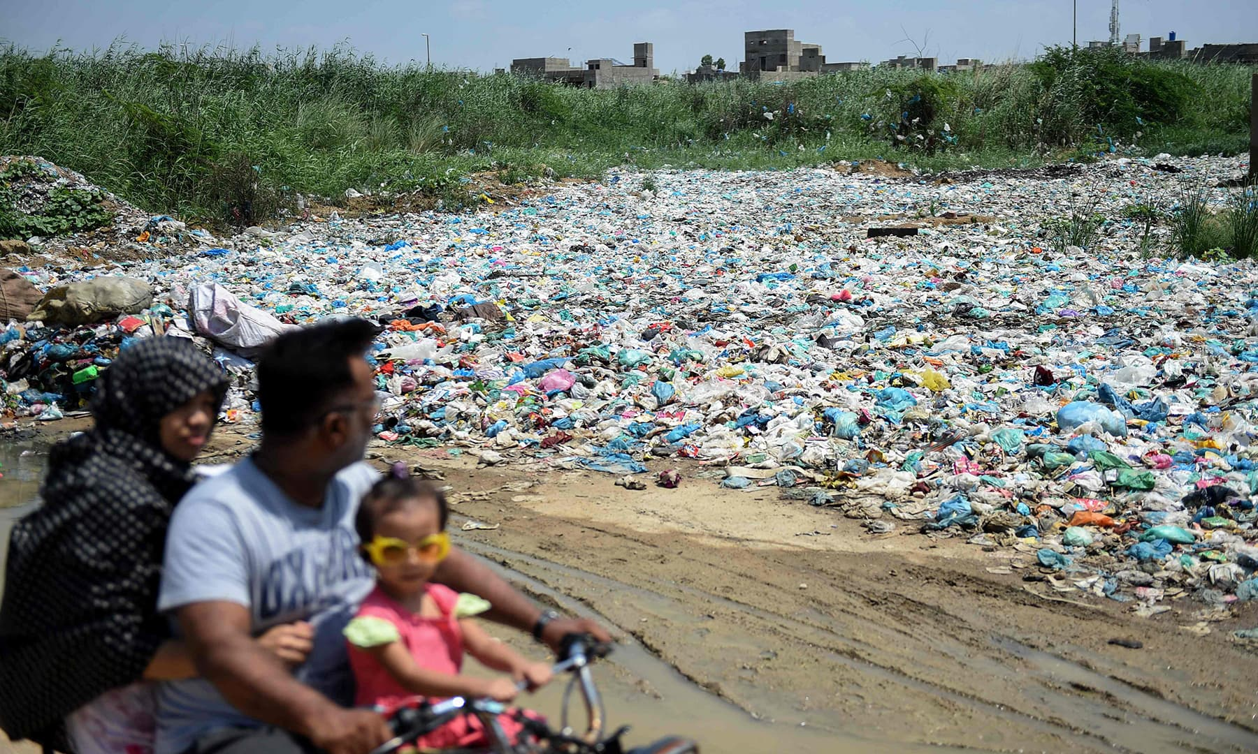 In this picture taken on September 4, a family rides past a garbage dump at a residential area in Pakistan's port city of Karachi. — AFP