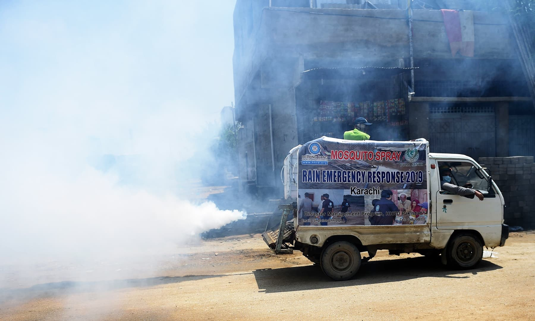 In this picture taken on September 4, municipal workers use a vehicle to fumigate a residential area in Karachi. — AFP