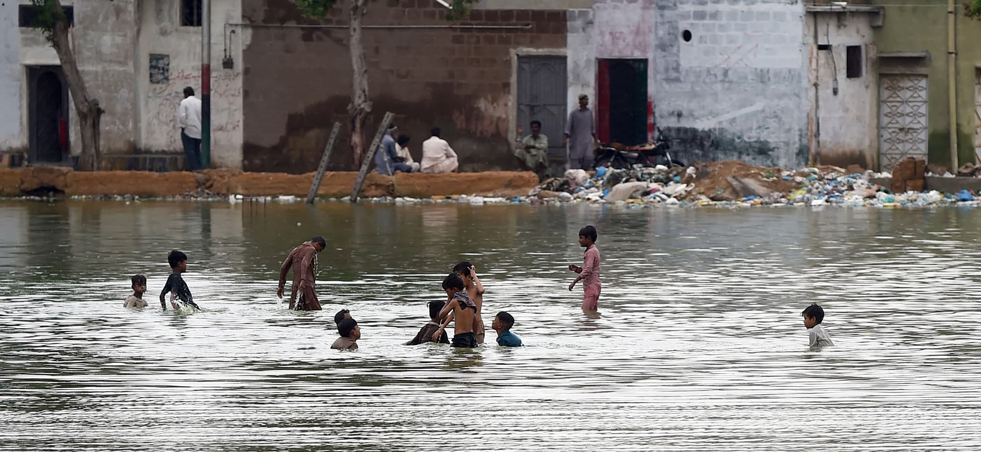 In this picture taken on September 2, 2019 children cool off in a pond of rain and waste water in Karachi. - Swarms of flies, water-borne illnesses, and rivers of sewage have brought Pakistan's Karachi to its knees this rainy season as decades of mismanagement have turned the country's commercial capital into a post-apocalyptic wasteland. (Photo by RIZWAN TABASSUM / AFP) / To go with 'PAKISTAN-HEALTH-WEATHER-FLIES,SCENE' by Ashraf KHAN — AFP or licensors