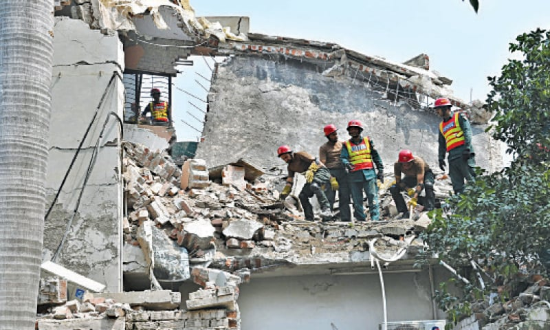 Rescue workers remove debris of the house to recover the family members after an oxygen cylinder blast in Iqbal Town. — White Star