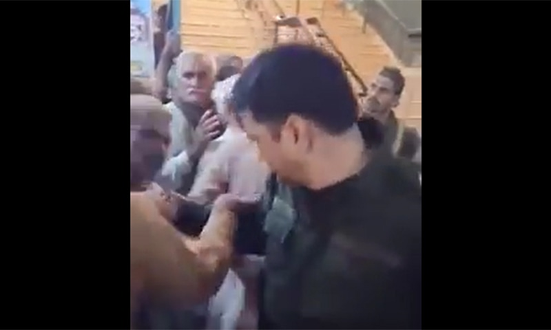 A screengrab of the video in which the officer can be seen grabbing the man's collar. — Twitter