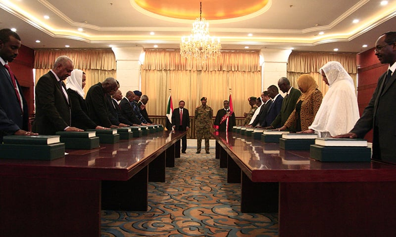 Members of the Sudanese cabinet take oath in the presence of the new Prime Minister Abdalla Hamdok (back- L) and General Abdel Fattah al-Burhan, the head of Sudan's ruling military council (back-C) at the presidential palace in the capital Khartoum, on September 8, 2019. - Sudan's first cabinet since the ouster of president Omar al-Bashir was sworn in today as the African country transitions to a civilian rule following nationwide protests that overthrew the autocrat. The 18-member cabinet led by Prime Minister Abdalla Hamdok, includes four women. (Photo by Ebrahim HAMID / AFP) — AFP or licens