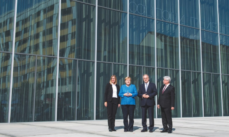 BERLIN: German Chancellor Angela Merkel, prime minister of Saxony-Anhalt Rainer Haseloff and mayor of Dessau-Rosslau Peter Kuras pose in front of the Bauhaus Museum Dessau during its opening on Sunday.—AFP