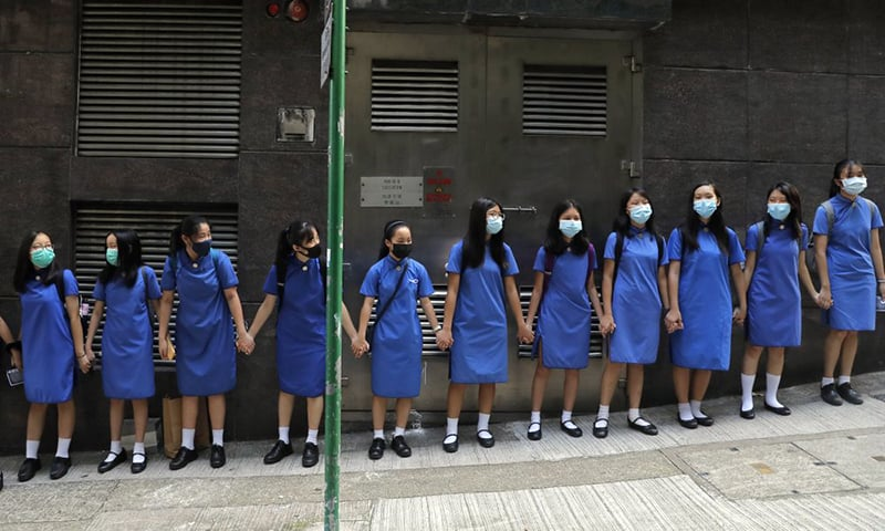 Students wearing mask hold hands to surround St. Stephen's Girls' College in Hong Kong on Monday. — AP