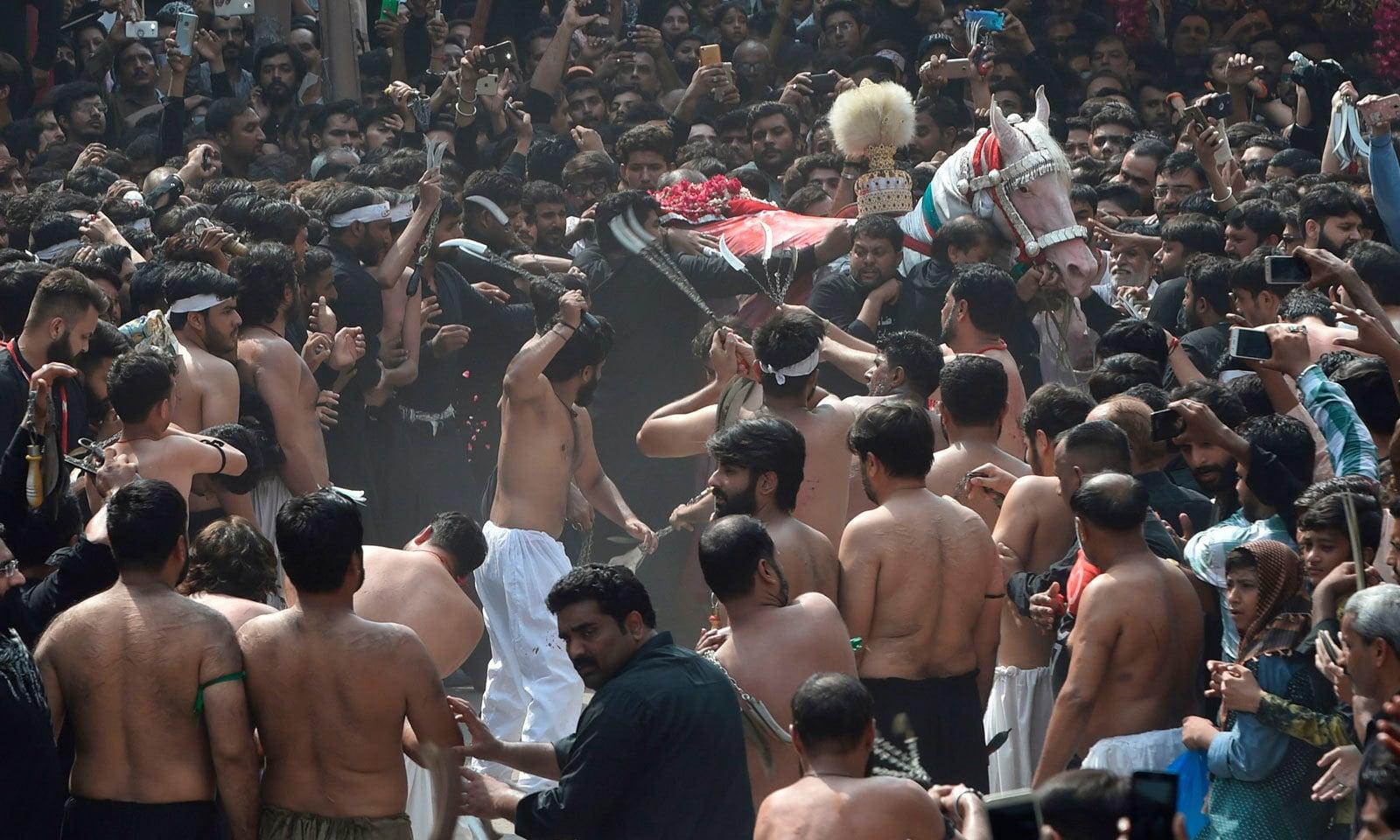 عزاداروں نے 9محرم الحرام کے جلوسوں میں زنجیر زنی، قمہ زنی اور سینہ کوبی کی— فوٹو: اے ایف پی