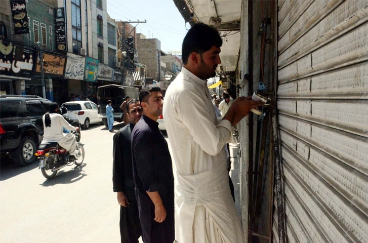 QUETTA: Security officials seal shops on a road as security was beefed up on Monday for Muharram processions.—PPI