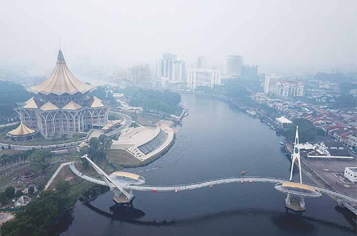 KUCHING (Malaysia): Haze shrouds an aerial view around Sarawak's assembly building (left) in Kuching, the capital of Sarawak state, on Monday.—AFP