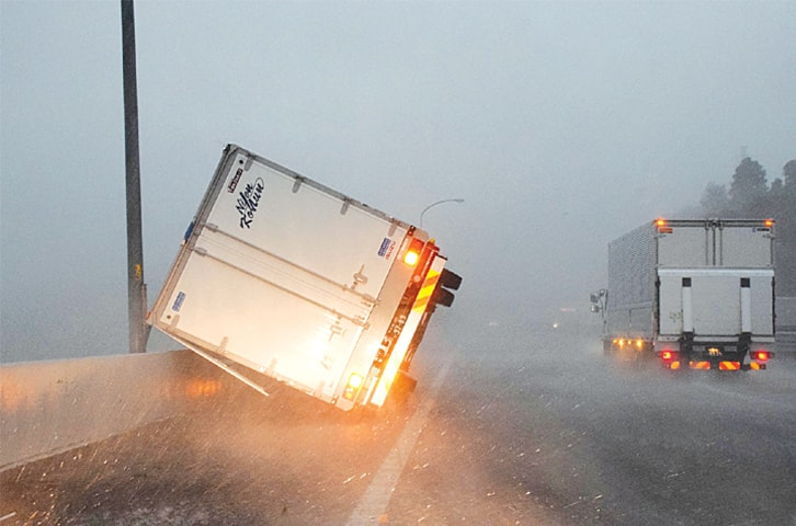 TOKYO: A truck turned over by high winds lies on a highway.—AFP
