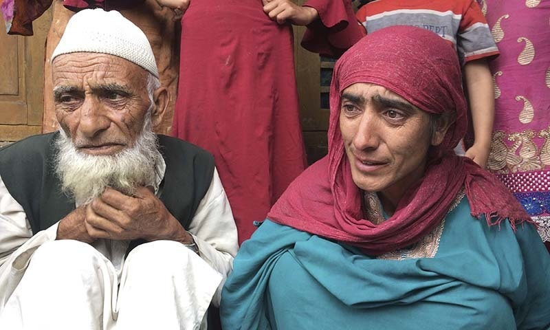 In this August 26 photo, a Kashmiri man Mohammed Abdullah sits with his daughter at their home and talks to reporters in tears about his grandson who was picked up in a nocturnal raid recently and shifted to a jail in Agra, in southern Karimabad village in occupied Kashmir. — AP