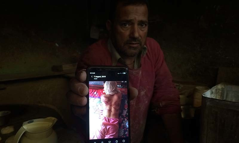 In this August 26 photo, a Kashmiri baker Sonaullah Sofi displays a photograph of his son after he was allegedly tortured by Indian army soldiers at their bakery in the southern village of Parigam in occupied Kashmir. — AP