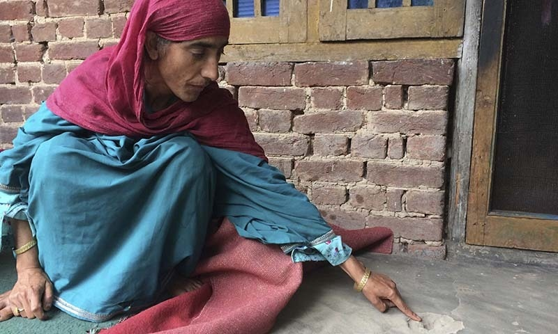 In this August 26 photo, a Kashmiri woman points her finger to a bullet mark allegedly caused by firing by an Indian army soldier who recently raided her home to arrest her young son in southern Karimabad village in occupied Kashmir. — AP