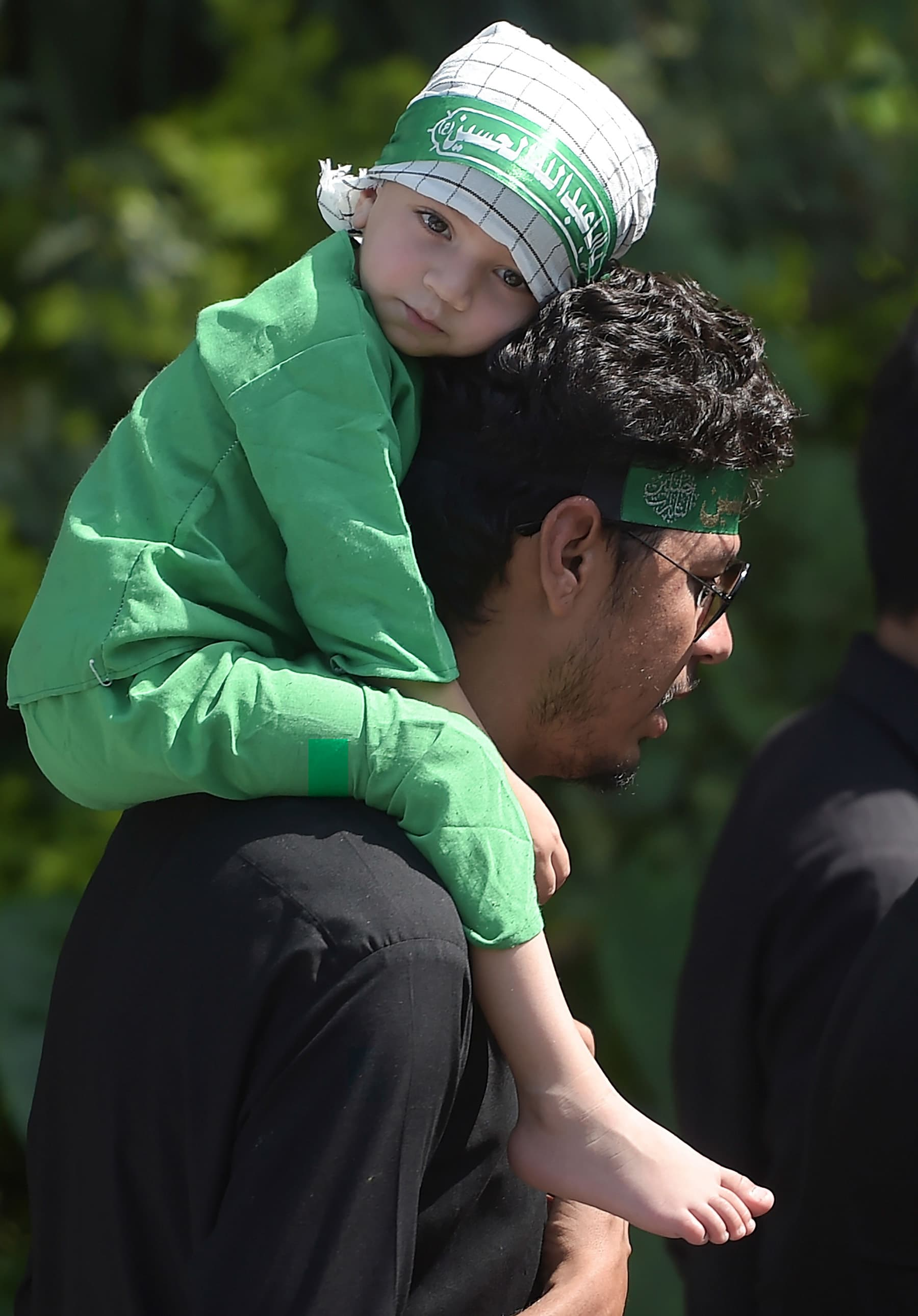 A participant holds his daughter on his shoulder as they march during a religious procession on the ninth day of Muharram in Islamabad on September 9. — AFP
