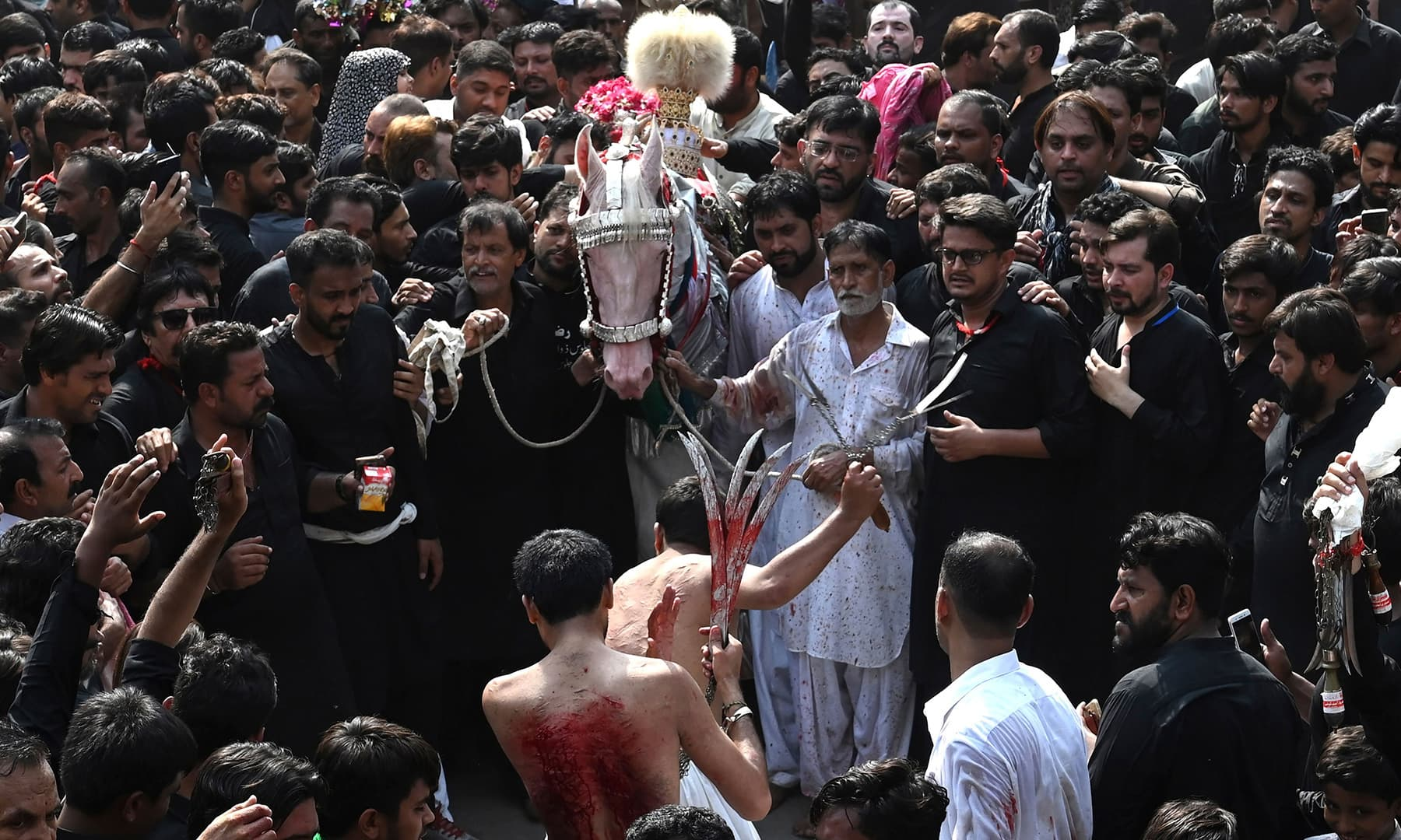 Mourners flagellate themselves during a religious procession on the ninth day of Muharram in Lahore on September 9. — AFP