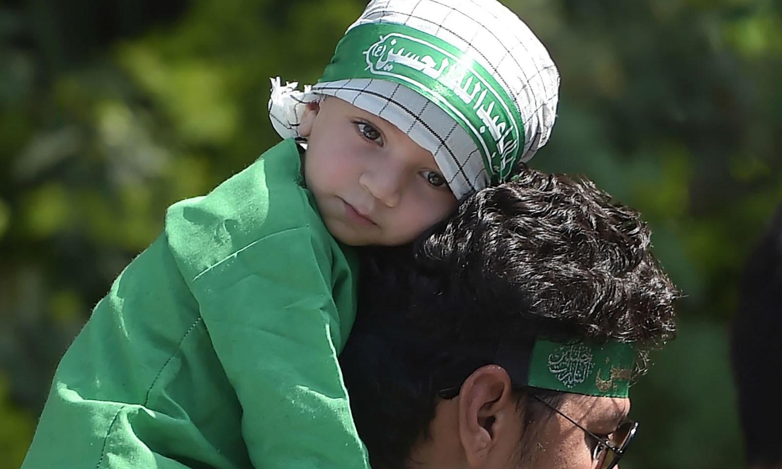 اسلام آباد میں یوم عاشور کے جلوس میں ایک بچی اپنے والد کے کندھے پر سوار ہے—فوٹو: اے ایف پی