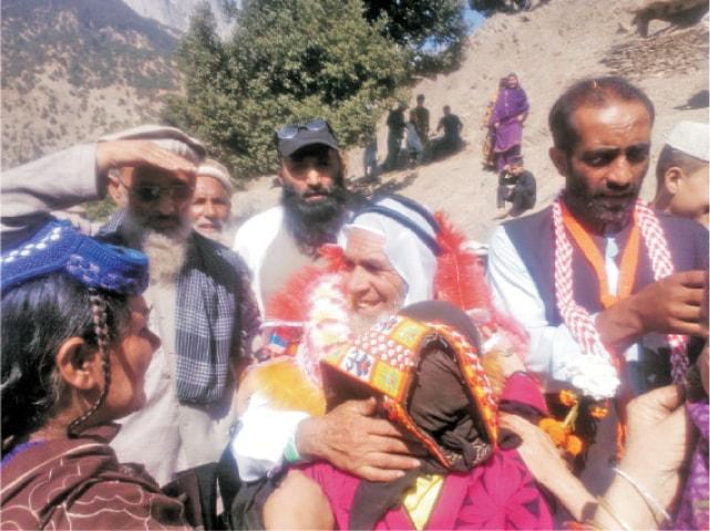 Haji Gulzar Khan being received by Kalash women on reaching Rumbur valley, Chitral. — Dawn