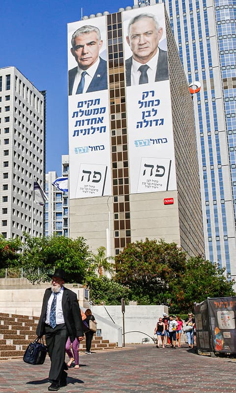 """An man walks along a street of Tel Aviv on September 12, 2019, as electoral billboards are seen in the background off the facade of a building showing the faces of (L to R) Yair Lapid and retired general Benny Gantz, two of the leaders of the """"Blue and White"""" (Kahol Lavan) electoral alliance vying for seats in the upcoming September 17 vote. — AFP"""