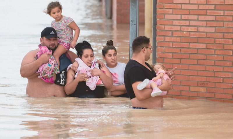 Almoradi: People carry children on a flooded street on Friday. — AFP