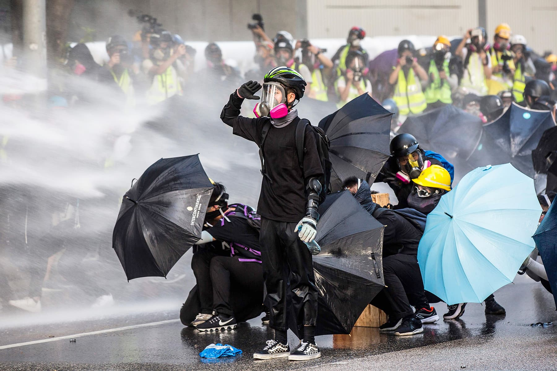 Pro-democracy protesters react as police fire water cannons outside the government headquarters in Hong Kong on Sunday. — AFP