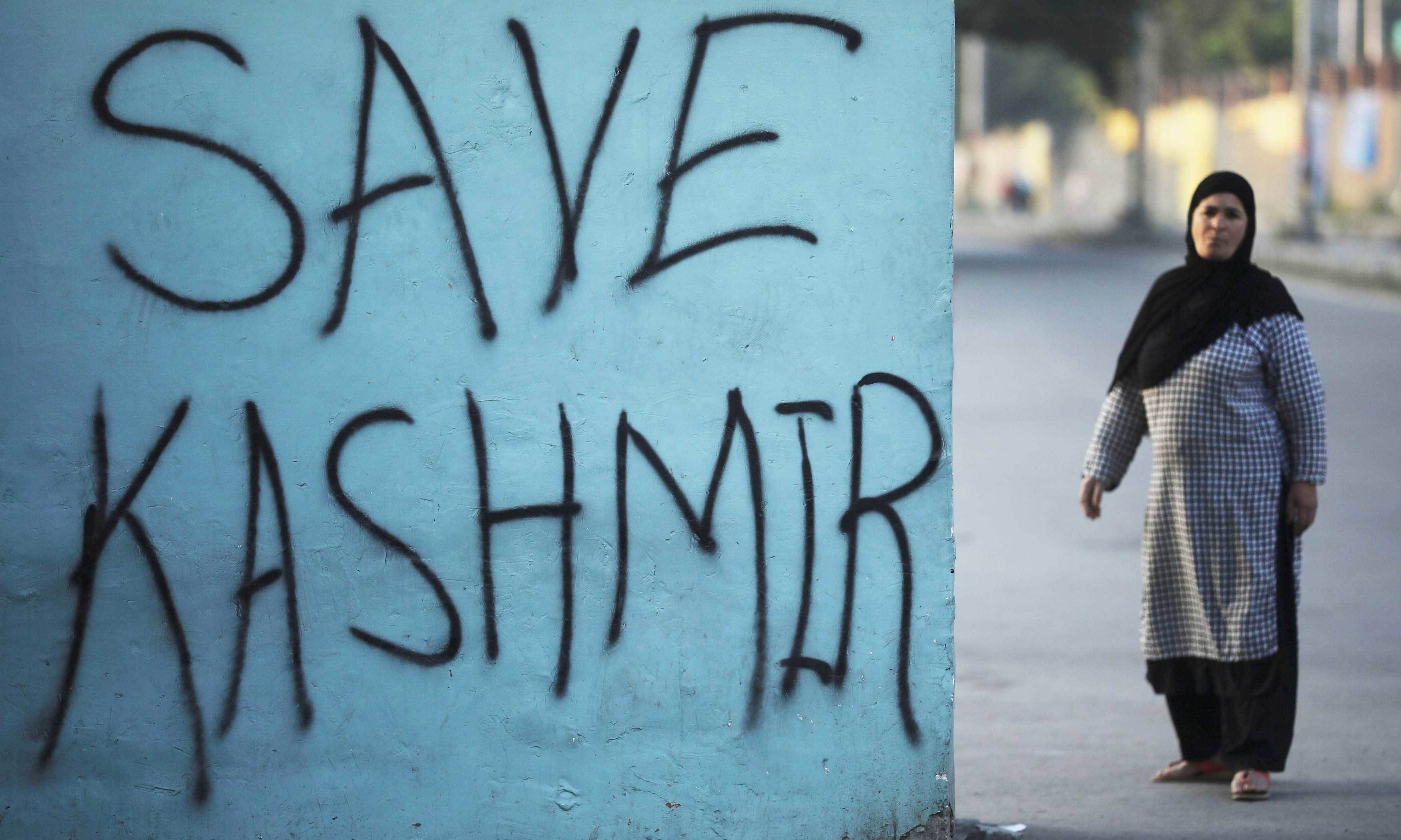 A Kashmiri woman stands next to a graffiti written on a wall during restrictions, in Srinagar, September 15. — Reuters