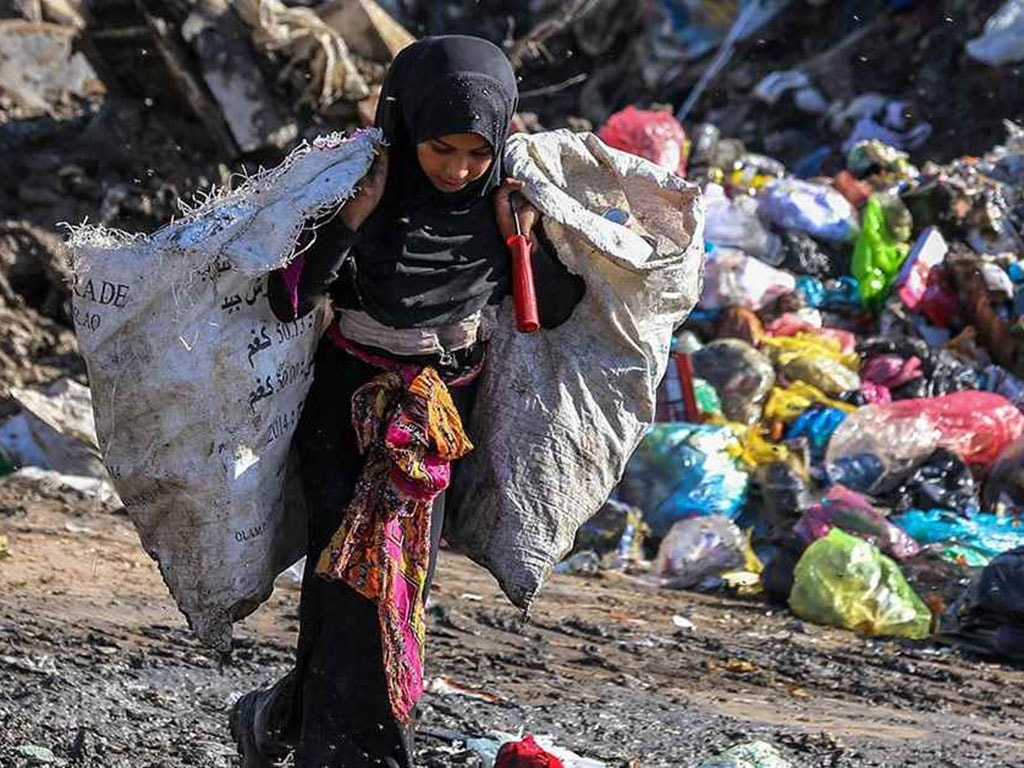 A girl collects recyclable items from garbage to earn a living for her family. — *Photo courtesy: UNICEF*