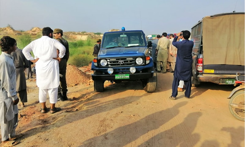Police and residents near the site where the minors' remains were found. — Photo: Wasim Riaz