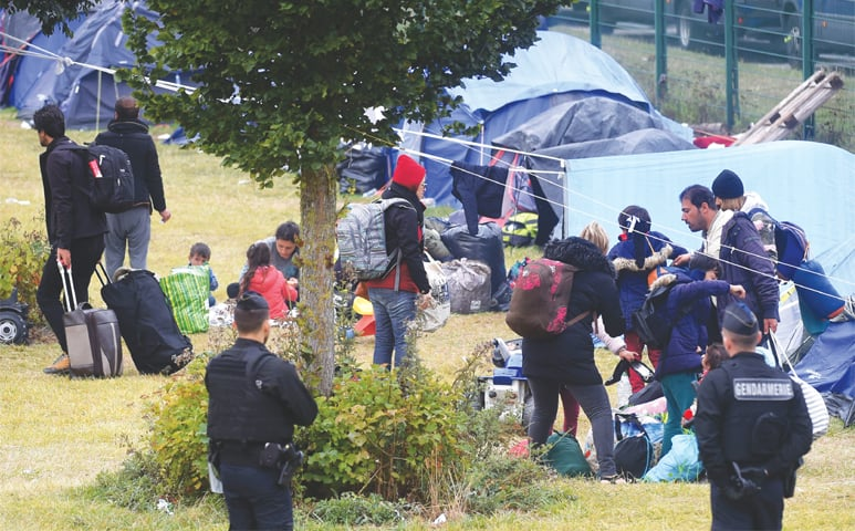 DUNKIRK: Migrants leave the camp during its evacuation by French police on Tuesday. — AFP